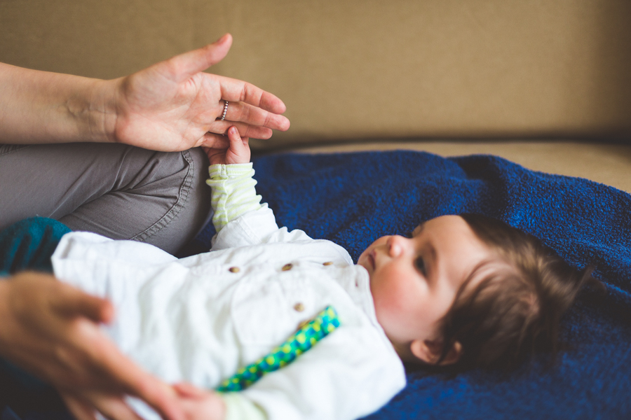 Baby liegt Zuhause vor Mama und berührt Hand
