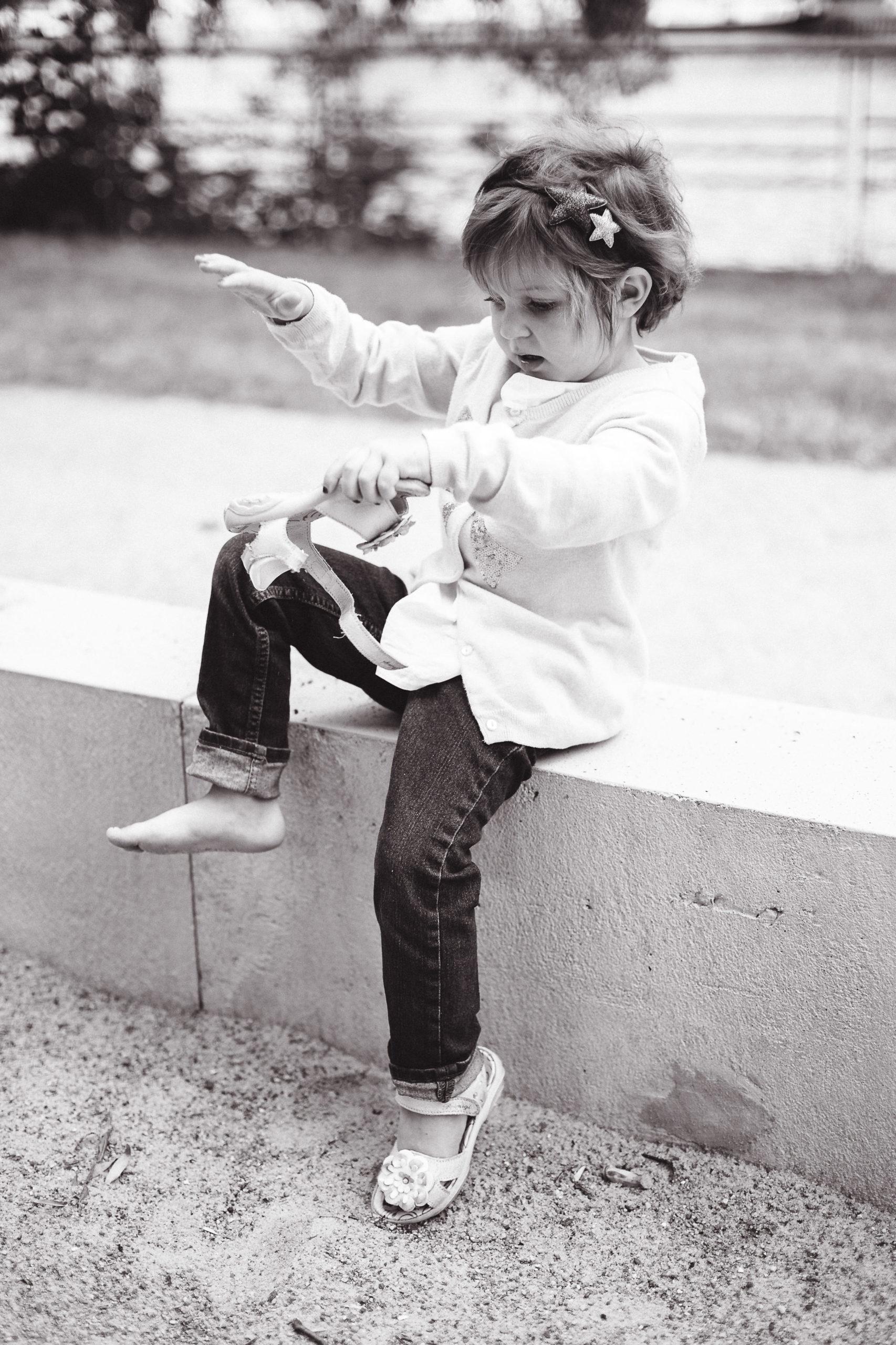 Mädchen schüttelt Sand aus ihren Sandalen