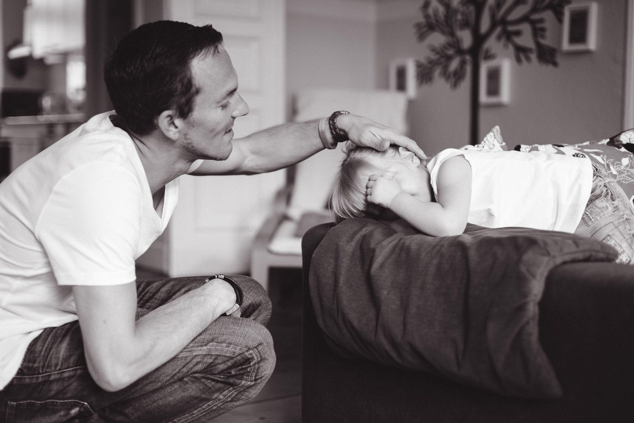 Papa streichelt Tochter liebevoll über den Kopf