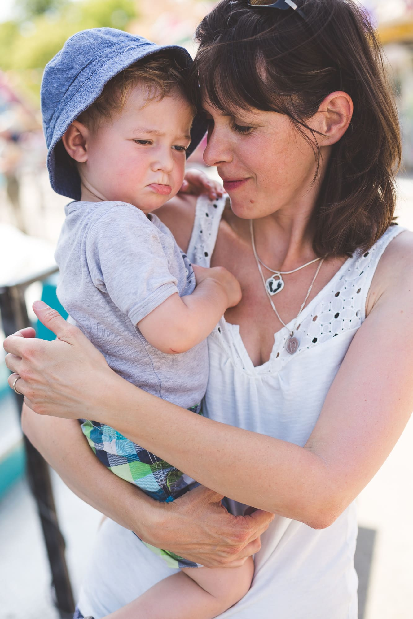 Kleiner Junge auf Mamas Arm ist traurig