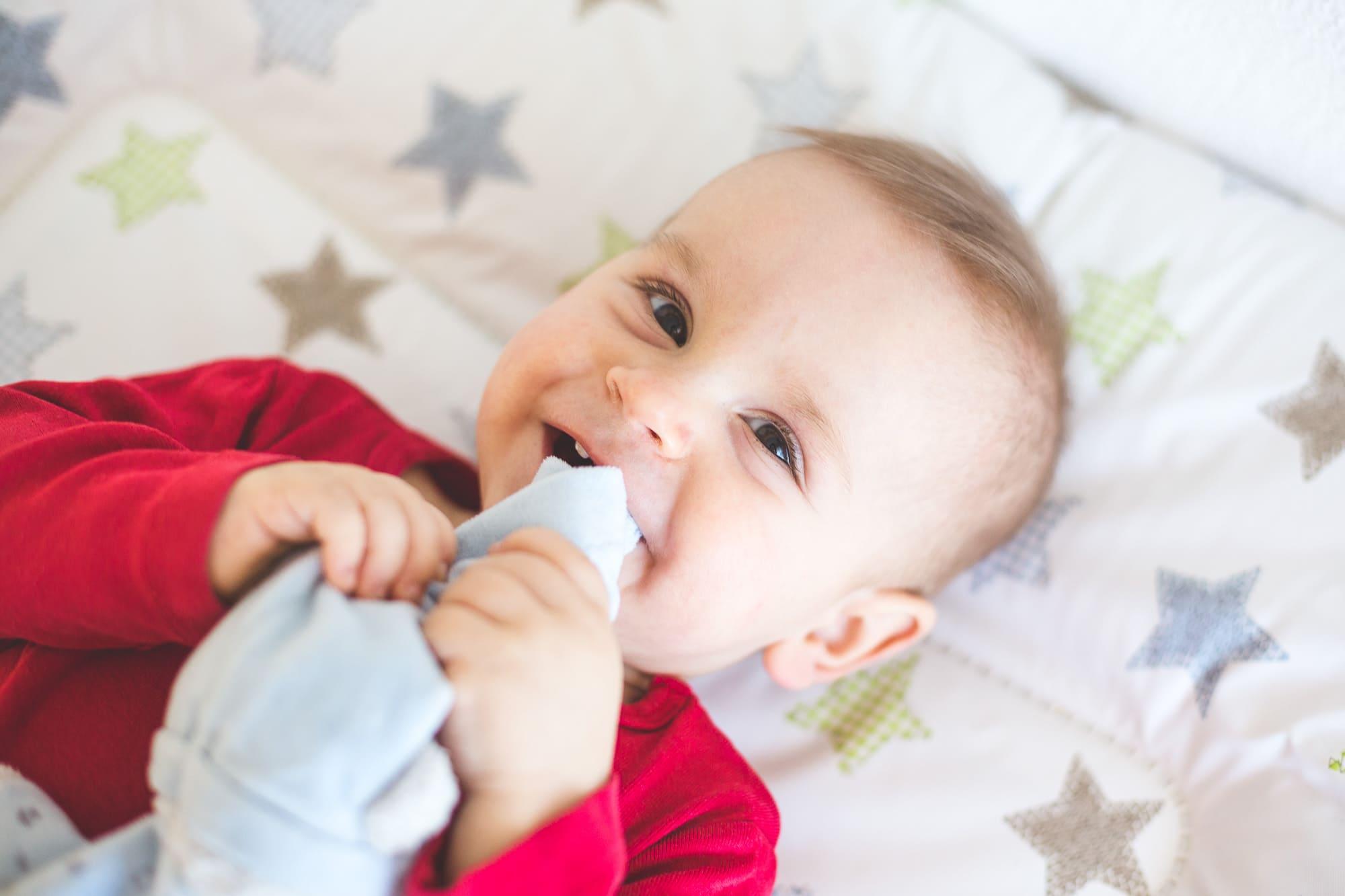 Kleiner Junge auf Wickeltisch lacht in die Kamera