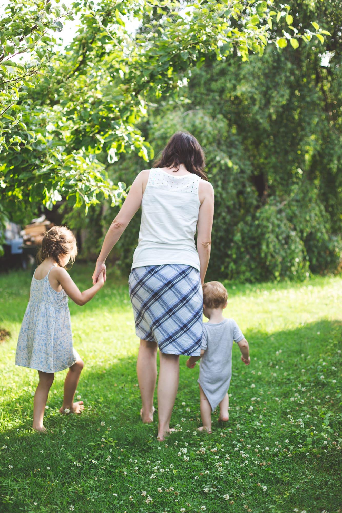 Mama mit Tochter und Sohn Hand in Hand im Garten