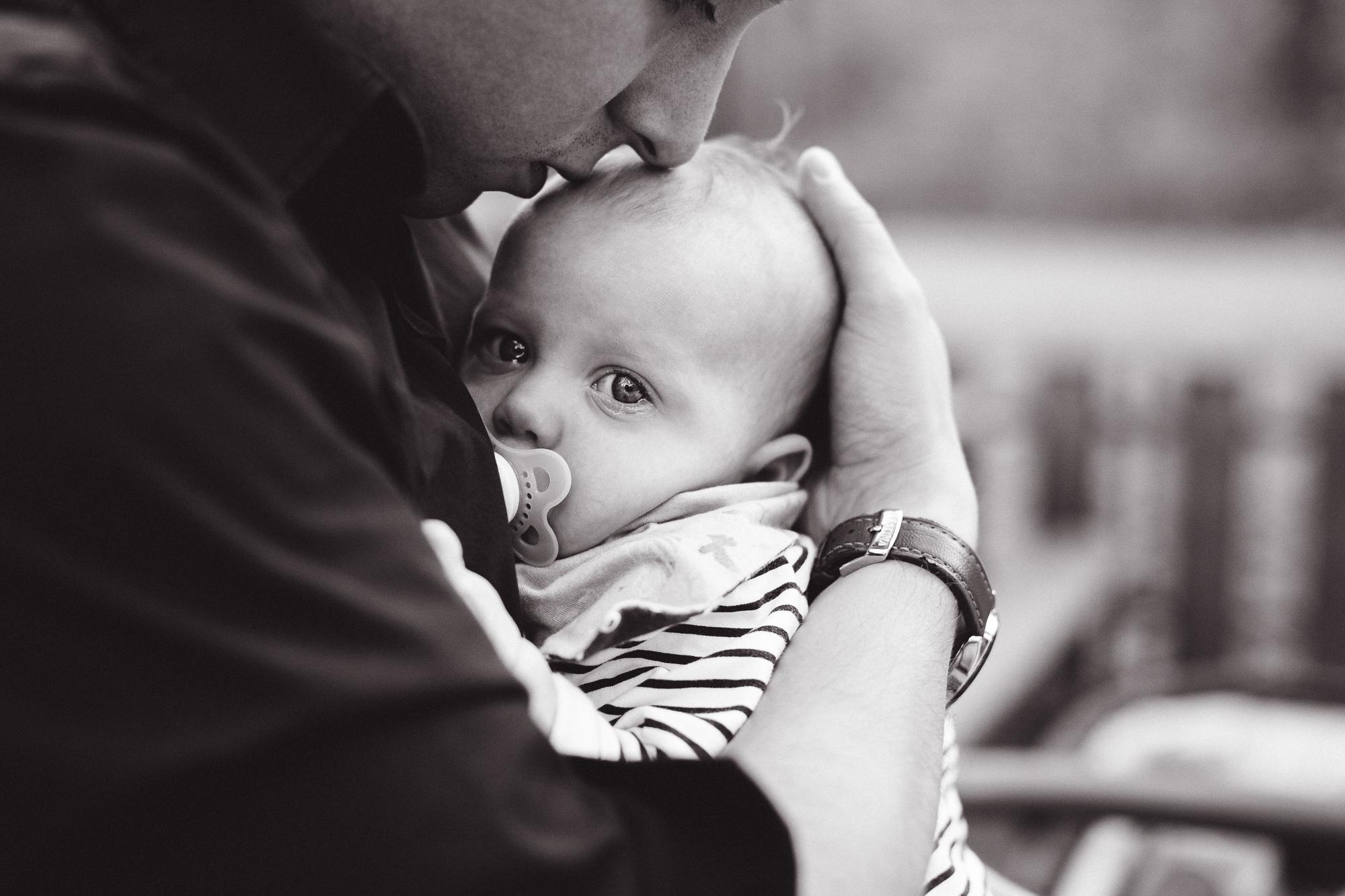Papa-Baby-Arm-weinend-Kuss